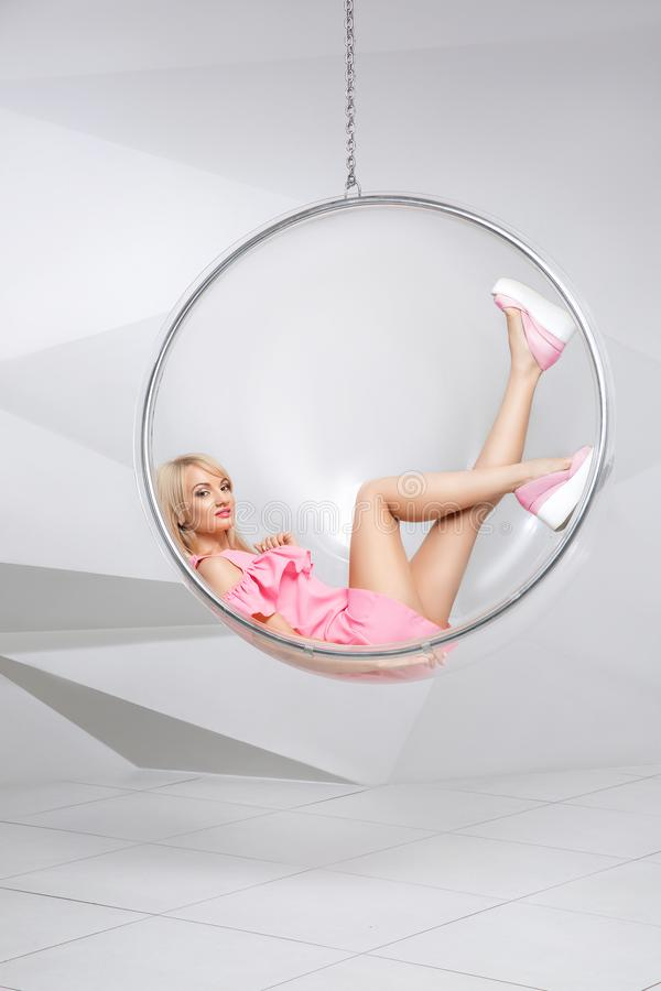 Young woman in a chair on a white background. Geometry. Blonde in a pink dress in a plastic round chair stock image
