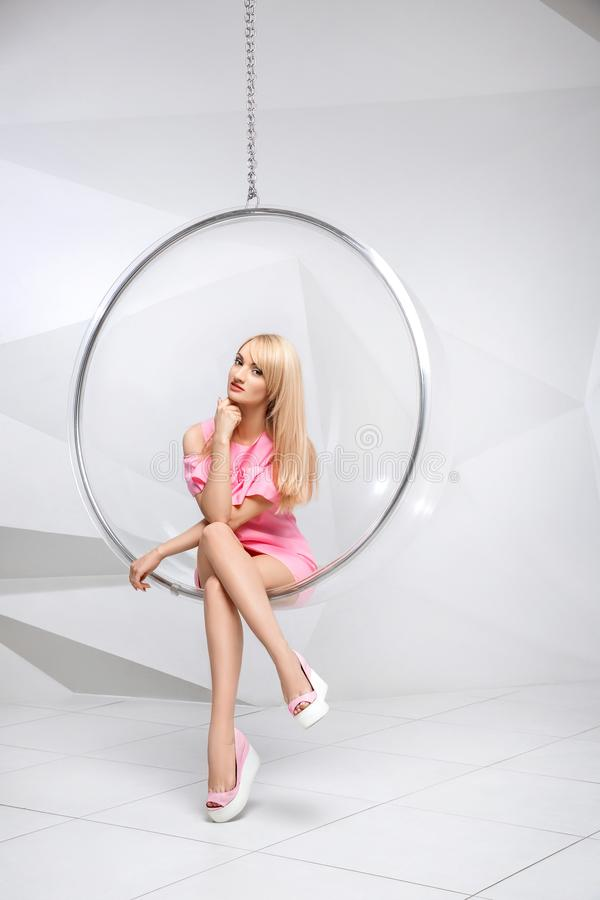 Young woman in a chair on a white background. Geometry. Blonde in a pink dress in a plastic round chair stock photos