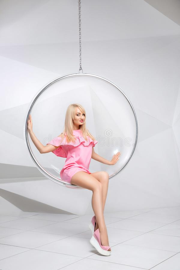 Young woman in a chair on a white background. Geometry. Blonde in a pink dress in a plastic round chair stock photo