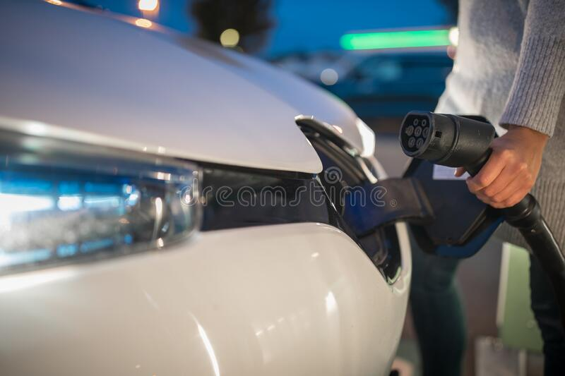 Young woman charging an electric vehicle stock photography