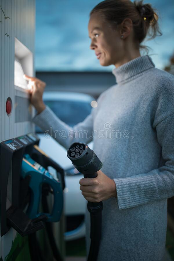 Young woman charging an electric vehicle royalty free stock photography