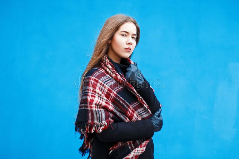 Young woman with a checkered red scarf near a blue wall stock photo