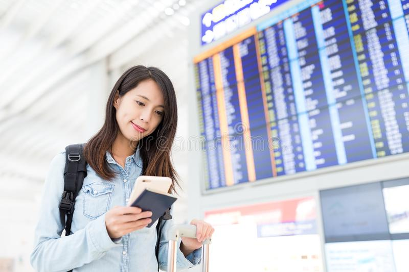 Young woman checking her flight on cellphone royalty free stock photo