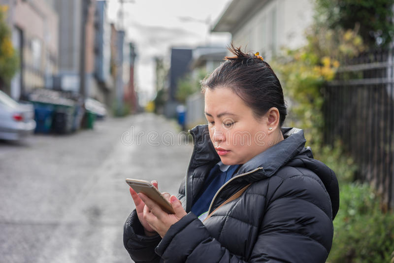 Young woman checking her messages her mobile phone royalty free stock image