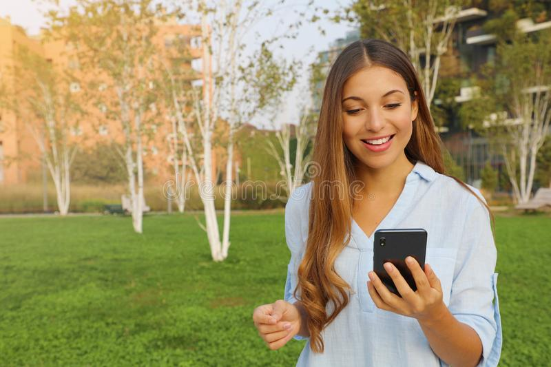Young woman checking her smart phone in city park stock image