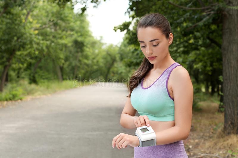 Young woman  pulse with medical device after training in park. Space for text royalty free stock photography