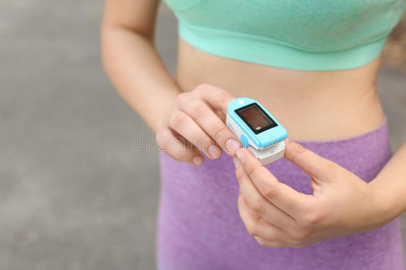 Young woman checking  with medical device after training on street, closeup. Space for text royalty free stock images