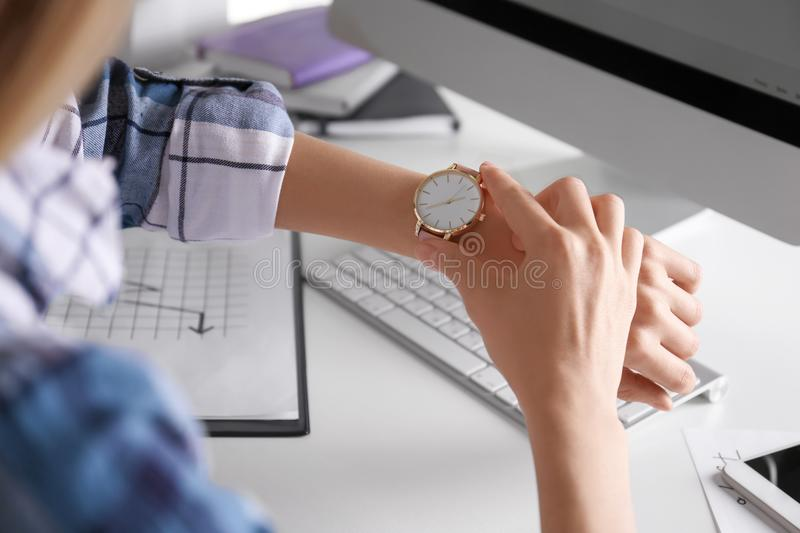 Young woman checking time on her wristwatch. At workplace stock images