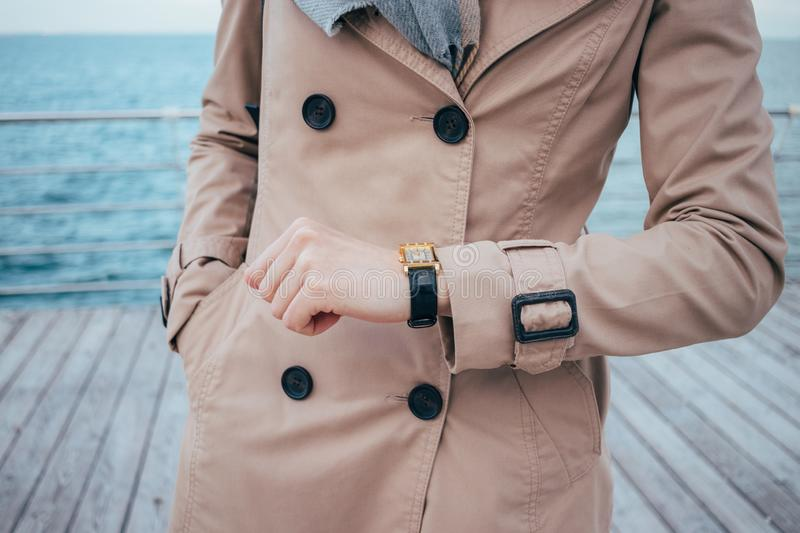 Young woman checking time on wrist watches stock image