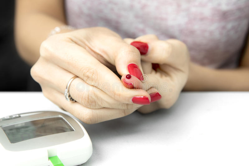 Young woman checks the amount of sugar. Hands of young woman checks the amount of sugar in the blood with a blood glucose meter stock photos