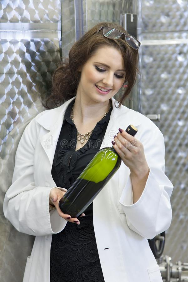 Young woman checks the cleanliness of bottle of white wine in winery royalty free stock photos