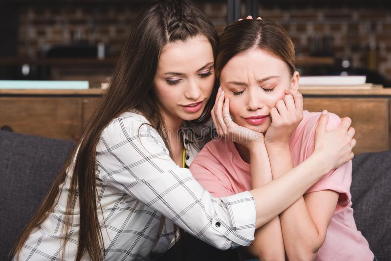 Young woman cheering up crying female friend. At home stock image