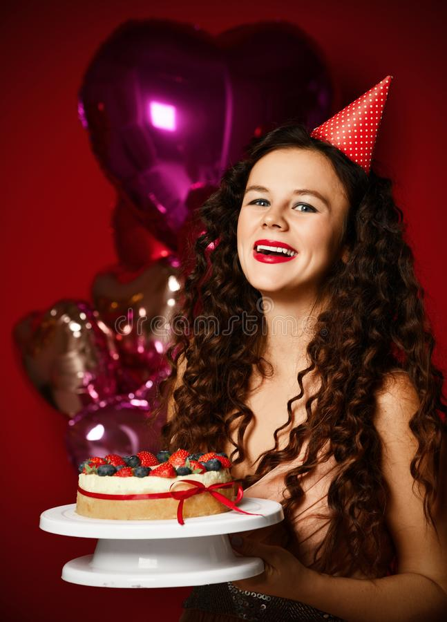 Young woman chef cook holding sweet cake with strawberry blueberry and cream smiling on dark red background stock image