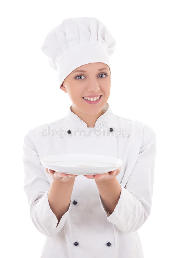 Young woman chef in uniform showing empty plate isolated on whi stock photos