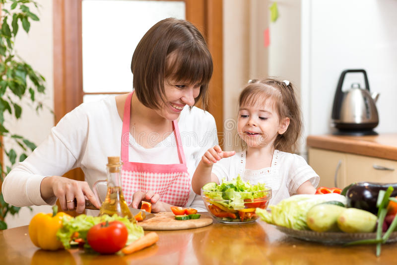 Young woman and child daughter making vegetable salad royalty free stock images