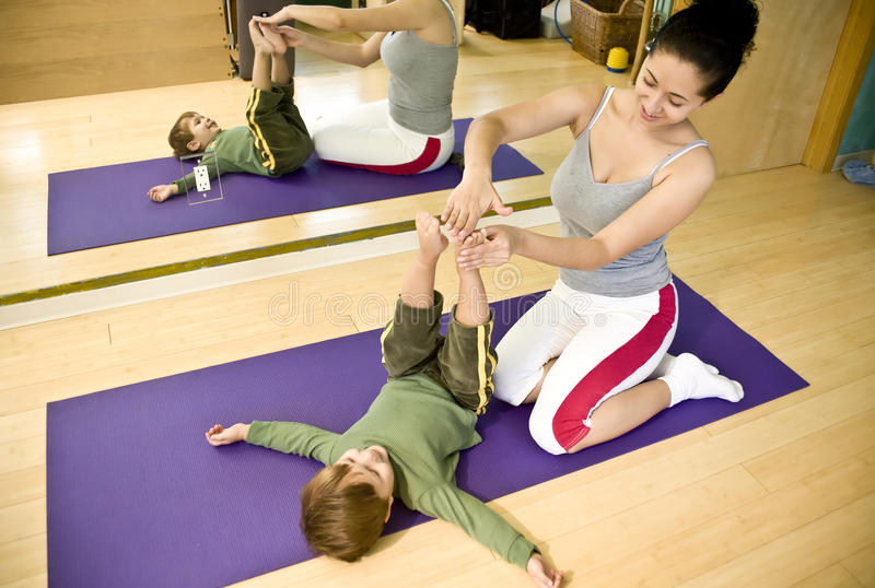 Young woman and child doing Pilates stock photography