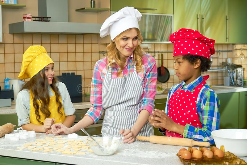 Young woman and children cooking. stock photo