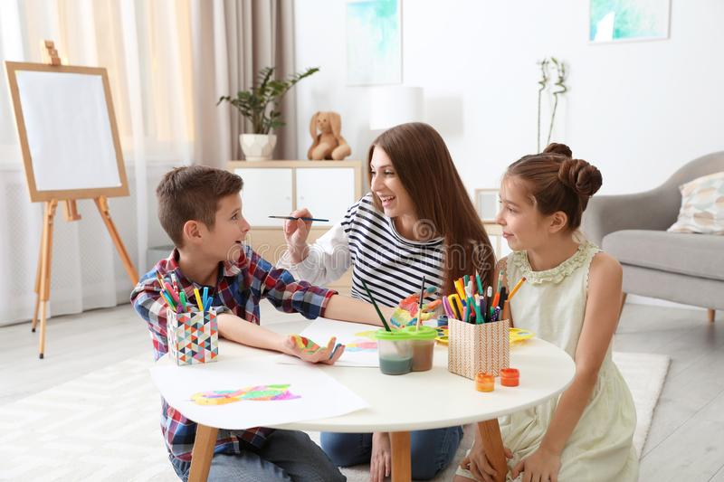 Young woman and children having fun with paints stock image