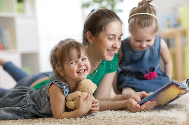 Young woman with children read storybook royalty free stock photos