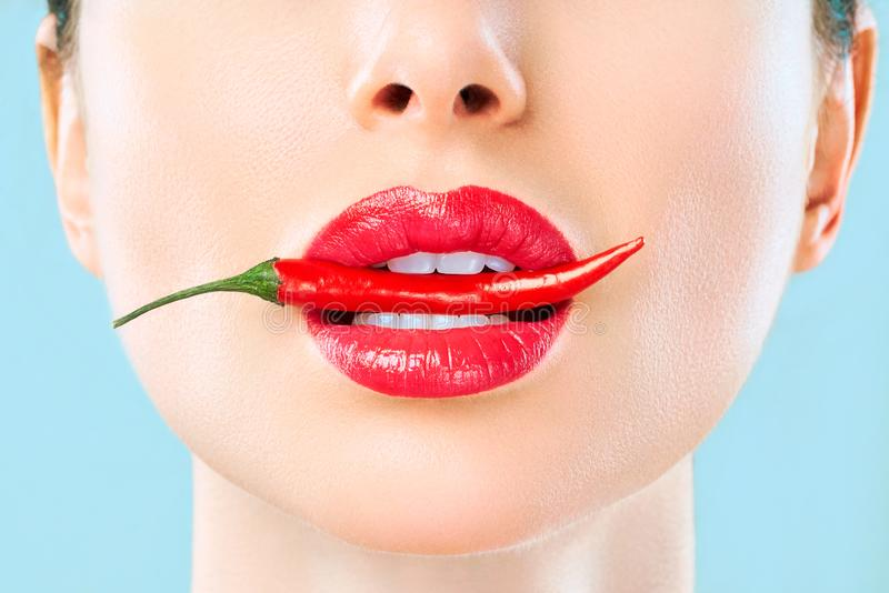 Young woman with chili red pepper isolated en blue background. Sexy female lips. Hot seductive girl royalty free stock photos