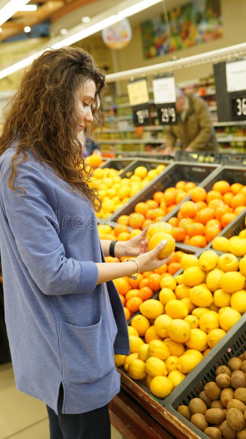 Young woman chooses fruits in grocer`s shop, touches to lemons, make purchases in supermarket, eats healthy food. People, stock images