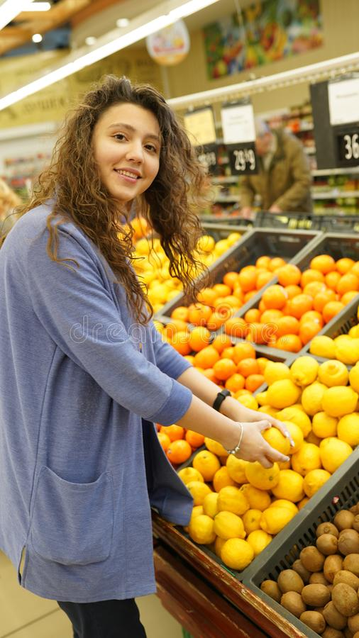 Young woman chooses fruits in grocer`s shop, touches to lemons, make purchases in supermarket, eats healthy food. People,. Consumerism and buying concept stock photography
