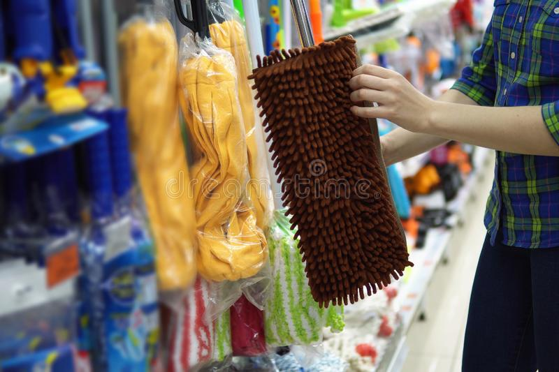 A young woman chooses a mop in the supermarket stock photography