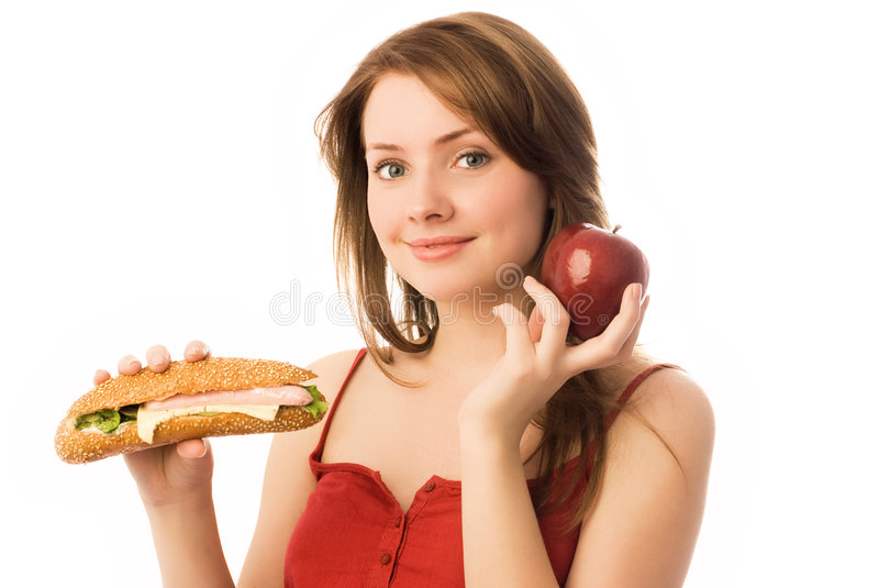 Young woman choosing between an apple and hot dog. Beautiful young woman choosing between an apple and hot dog stock images