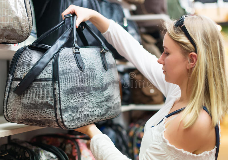 Young woman choosing bag. royalty free stock images