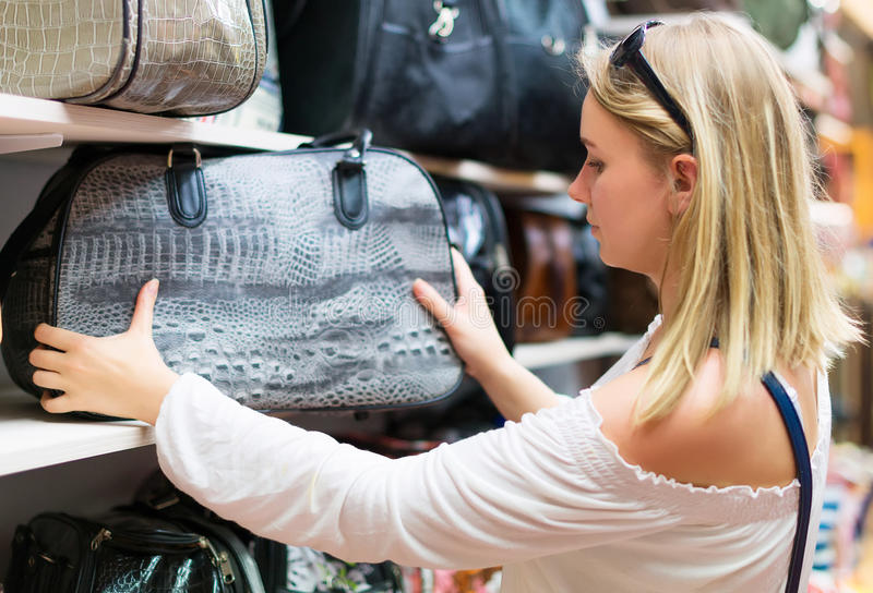 Young woman choosing bag. royalty free stock photos