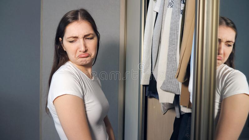Young woman choosing clothes in wardrobe at home stock photo