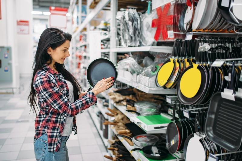 Young woman choosing frying pan in supermarket stock image