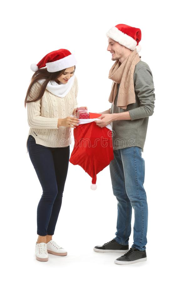 Young woman choosing gift from Christmas bag held by her husband on white background stock photos