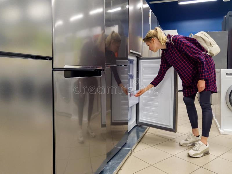 Woman choosing new refrigerator in household appliances store. Young woman choosing new refrigerator in household appliances store stock photos