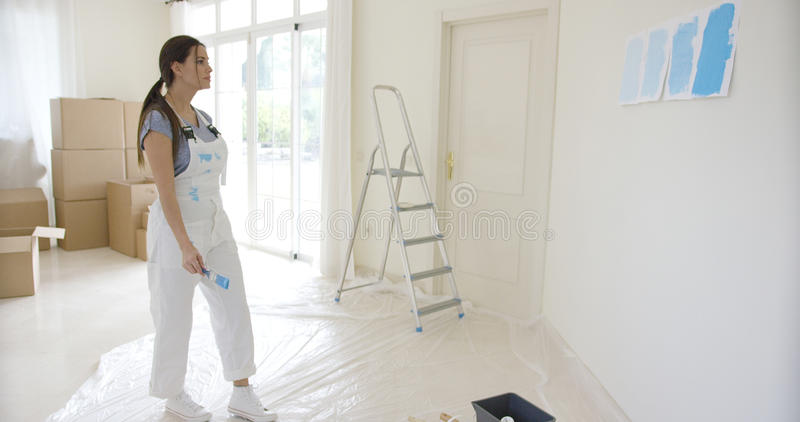 Young woman choosing a paint color for decorating stock image