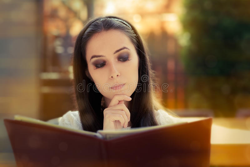 Young Woman Choosing from a Restaurant Menu royalty free stock photo