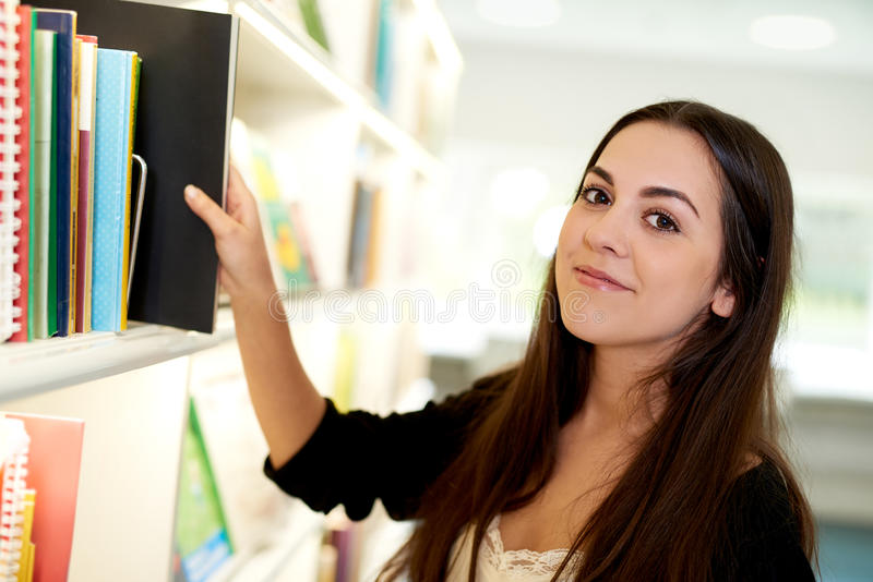 Young woman choosing the right file from the shelf stock image