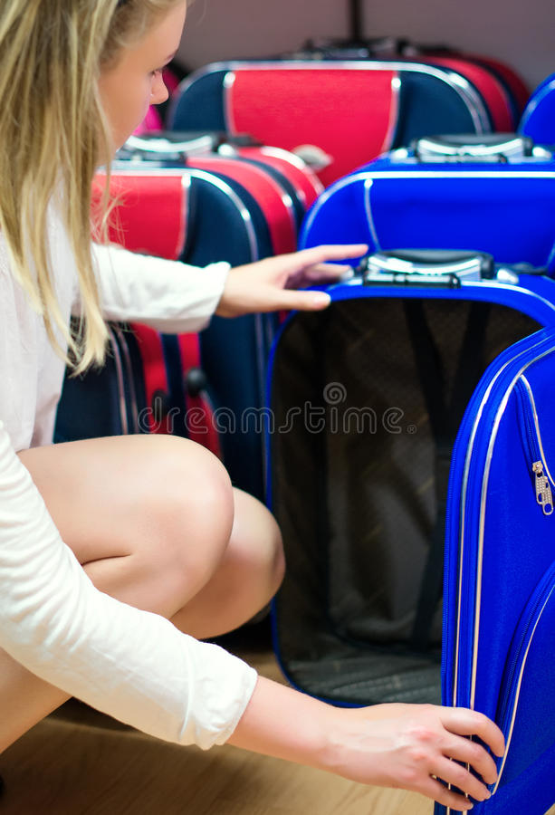 Young woman choosing travel suitcase. stock images