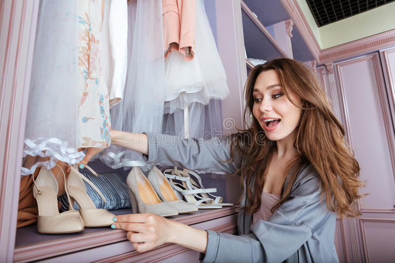 Young woman choosing what to wear in a closet stock photography