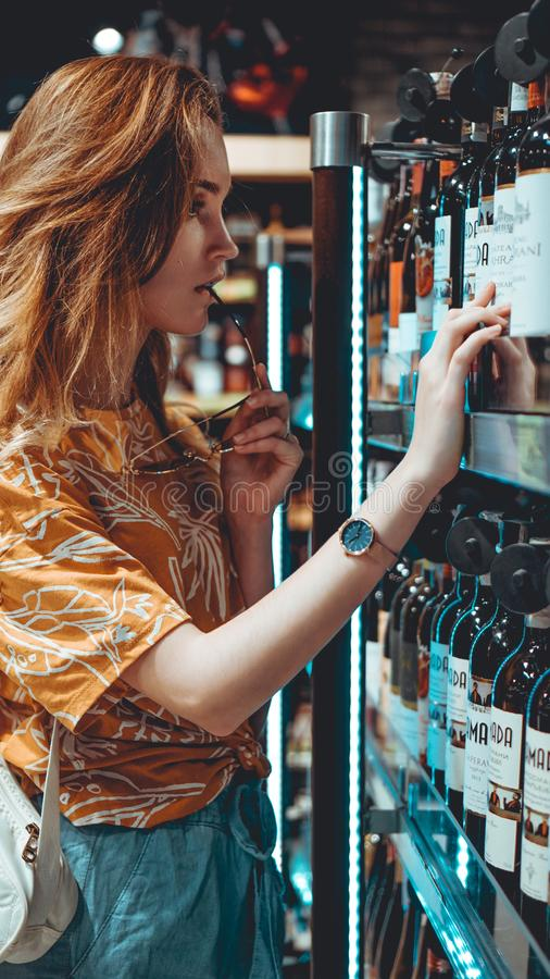 Young woman is choosing wine in the supermarket. royalty free stock image