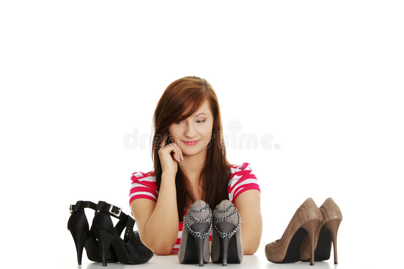 Young woman chosing shoes stock photography