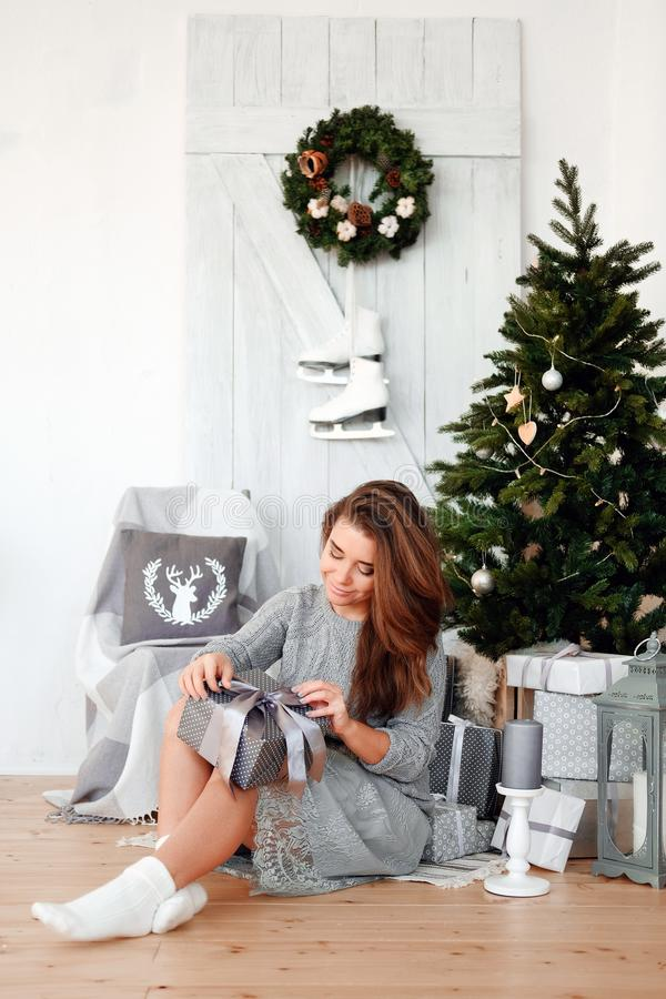 Woman in Christmas decoration opens boxes with gifts under the tree royalty free stock photography