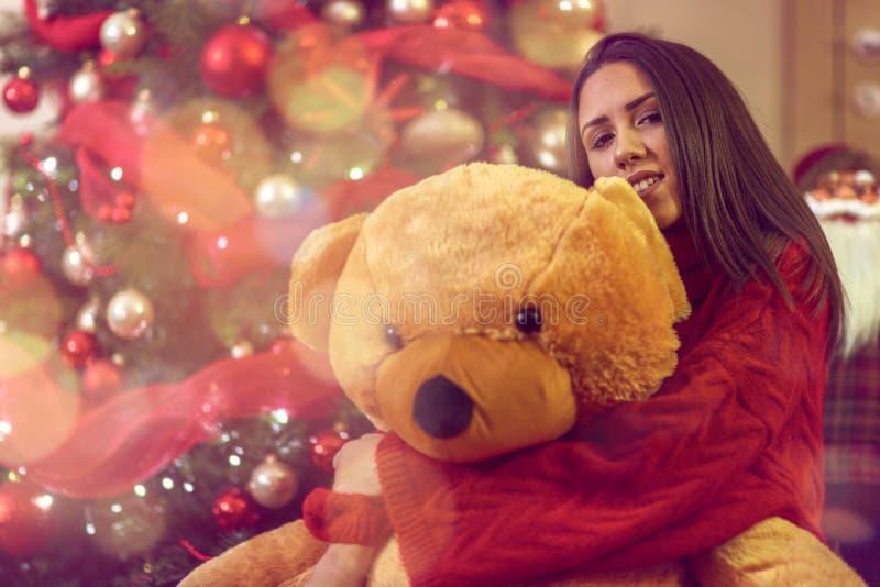 Young woman with Christmas gift.Girl hugs teddy bear present royalty free stock photo