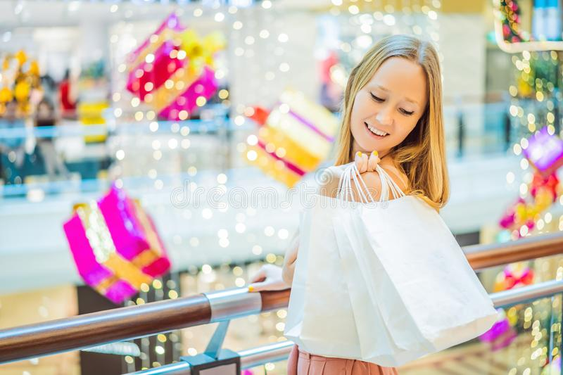Young woman in Christmas mall with Christmas shopping. Beauty bu. Y Christmas night shopping discounts royalty free stock image