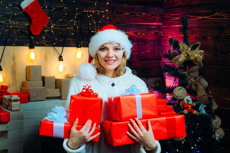 Young woman with christmas present boxes in front of christmas tree. Young woman wink. Funny christmas girl. Crazy royalty free stock photos