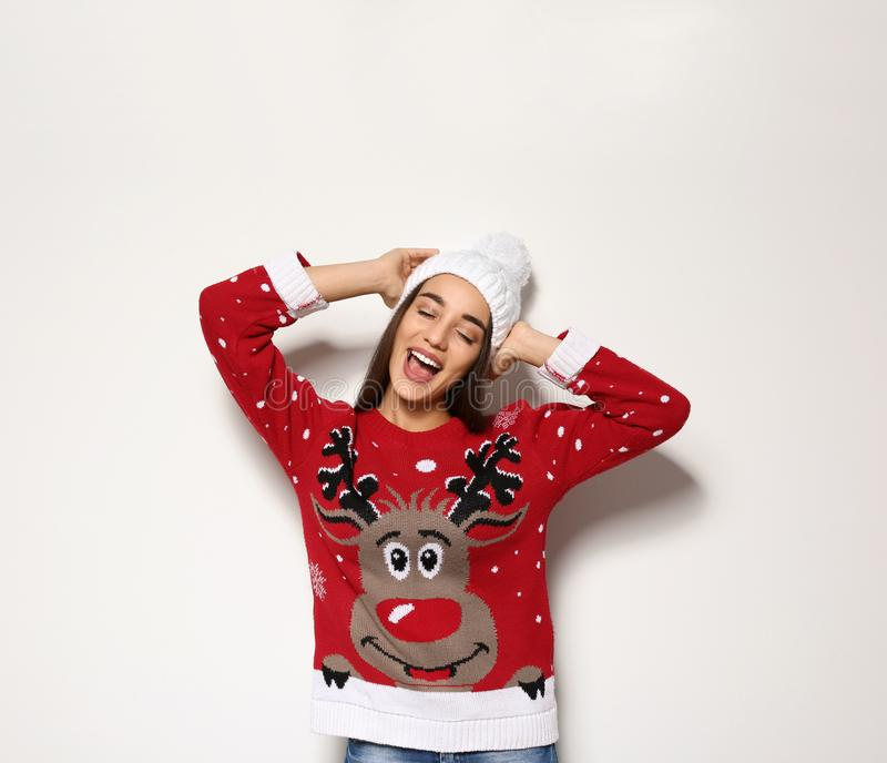 Young woman in Christmas sweater and knitted hat. On white background stock photos
