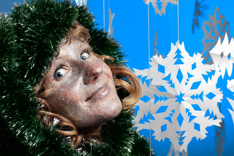 Young woman in Christmas tree decorations and glistering make up. Young bizarre woman in Christmas tree decorations and glistering make up smiling looking at royalty free stock images