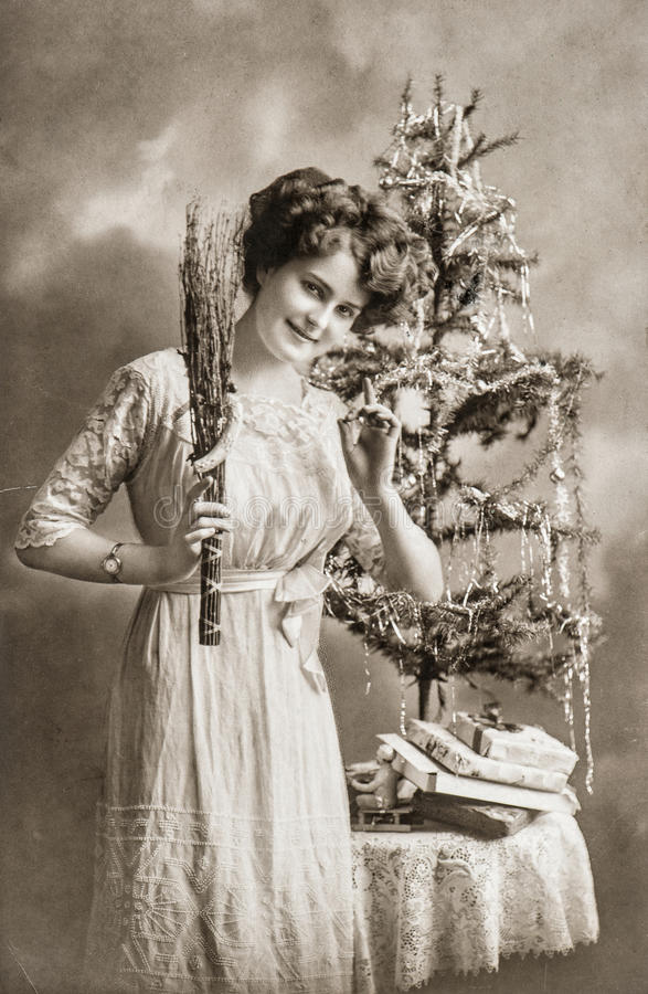 Young woman with christmas tree and gifts. Antique picture stock images