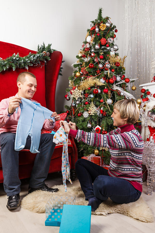 Young woman at the Christmas tree unpacking presents stock photography
