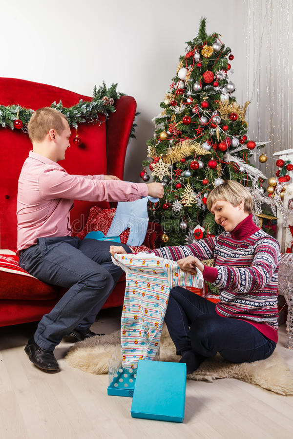 Young woman at the Christmas tree unpacking presents royalty free stock photos